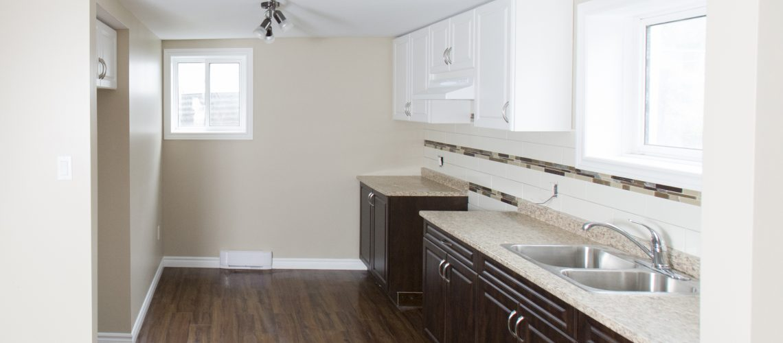 A newly renovated basement suite with a kitchen.